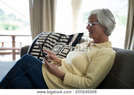 Senior woman using digital tablet on sofa in living room