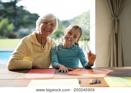 Smiling granddaughter and grandmother drawing in the deck shade near the pool