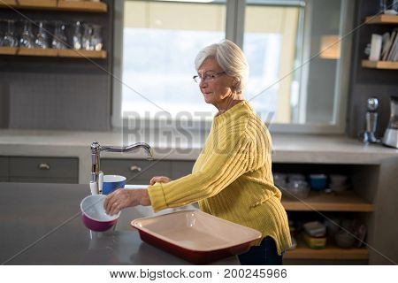 Senior women picking up a bowl in the kitchen