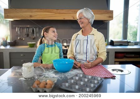 Smiling grandmother and granddaughter looking at each other in the kitchen