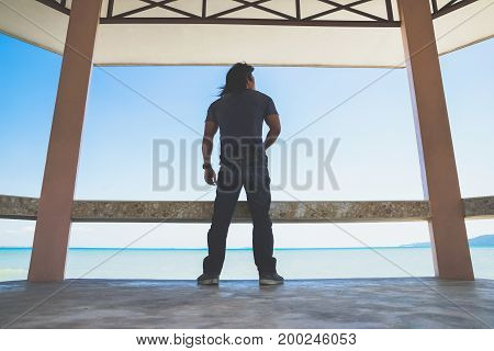An Asian man stand turn his back under roof next to the sea