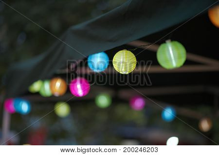 Many Colorful Small Paper Lanterns on a Tent at Night