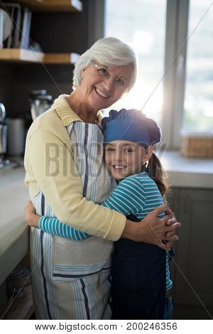 Smiling grandmother and granddaughter embracing in the kitchen