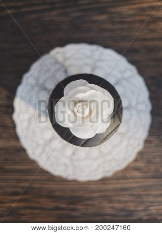 Homemade cupcake with flower against a wood background