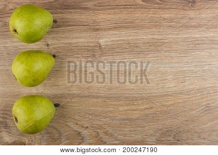 Row Of Pears From Left Side Of Wooden Table