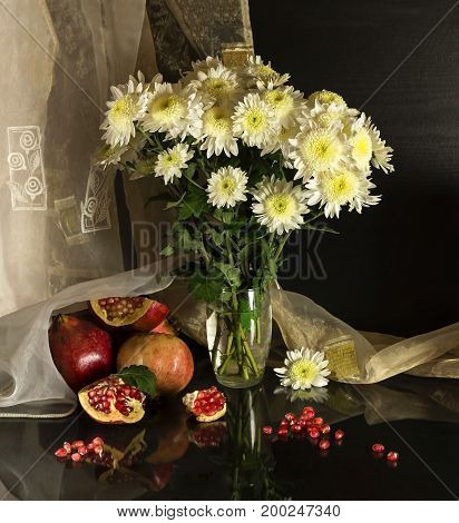 Still life with chrysanthemums and grenades on the table closeup