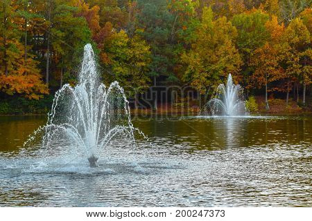 Two fountains in a pond surrounded by trees turning colors