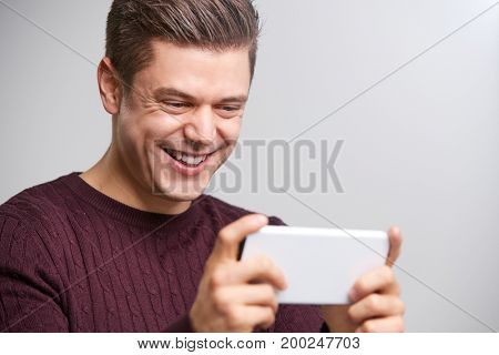 Close up of young white man taking selfie with a smartphone