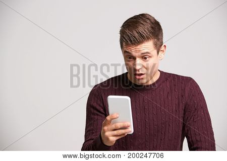 Portrait of a shocked young white man using a smartphone