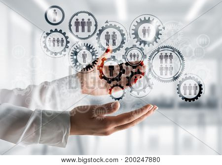 Business woman in white shirt keeping black social gear icons in hands with office view on background. Mixed media.