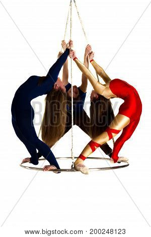 Young woman`s trio doing som acrobatic tricks on aerial luster