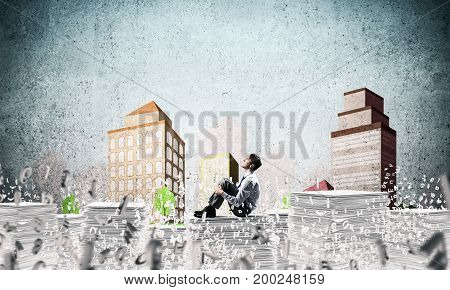Thoughtful businessman looking away while sitting among flying letters with drawn cityscape on background. Mixed media.