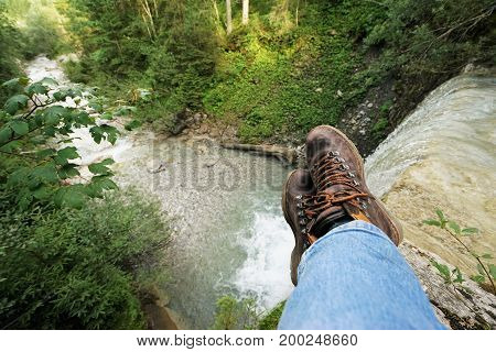 Young man resting at a waterfall, you can see the mountain boots