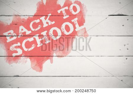 Back to school text on green and blue splash against white wood