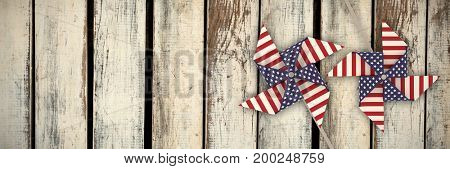 3D image composite of pinwheel with American flag pattern against wood panelling in pattern