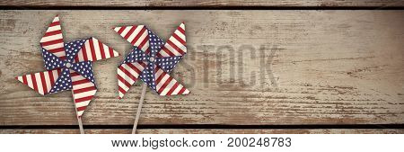 3D image composite of pinwheel with American flag pattern against wood panelling