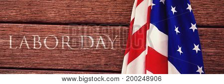 Labor day text  against american flag on a wooden table