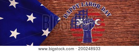 Happy labor day text over cropped hand holding tools against american flag on a wooden table