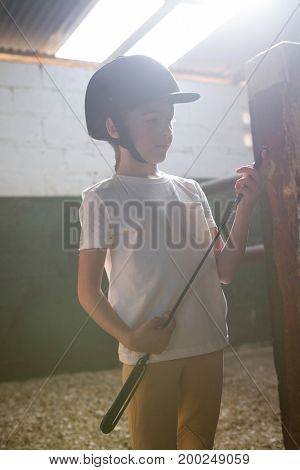 Thoughtful girl holding crop stick in stable