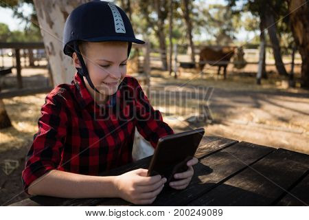 Girl using digital tablet while sitting