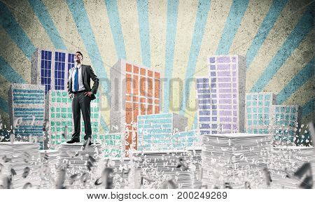 Confident businessman in suit standing on pile of documents among flying letters with drawn cityscape background. Mixed media.