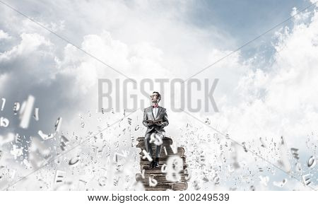 Funny man in red glasses and suit sitting on book in blue sky