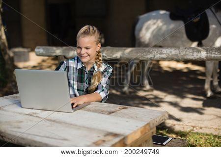 Girl using laptop while sitting