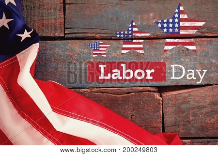 Composite image of labor day text with star shapes American flag against american flag on old wooden table