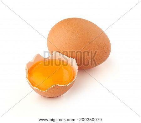 Yolk of egg in broken eggshell and whole egg