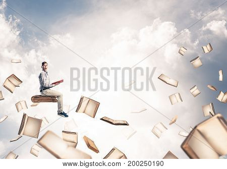 Young shocked man floating in blue sky with red book in hands