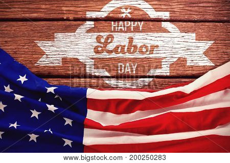 Digital composite image of happy labor day banner against american flag on a brown table