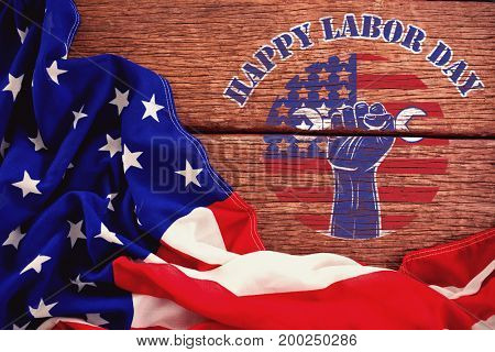 Happy labor day text over cropped hand holding tools against crumbled american flag on wooden table
