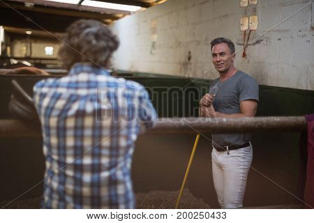 Two men interacting with each other while working in the stable