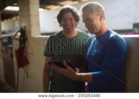 Two male friends using digital tablet in the stable