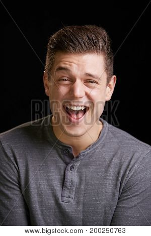 Laughing young white man looks to camera, vertical portrait