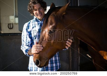 Smiling man caressing the brown horse in the ranch