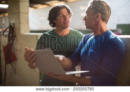 Two male friends using laptop in the stable