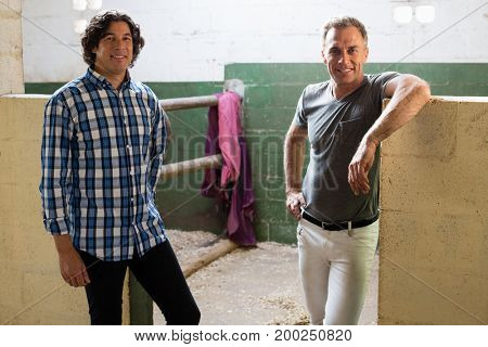 Two smiling male friends standing together in the stable