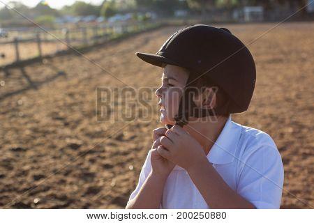 Boy removing helmet on a sunny day