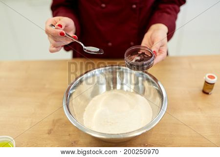 cooking, baking and people concept - chef hands with flour in bowl and food color additive making batter or dough