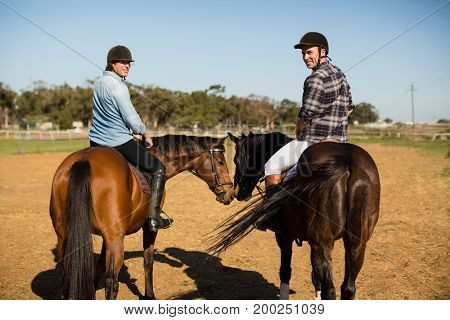 Two male friends riding horse in the ranch on a sunny day