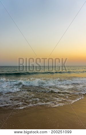View on a Beach in the Morning Light of a beautiful beginning Sunrise. Close-up of long deserted Beach in Summer. Beach Background.