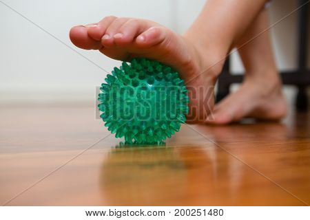 Low section of girl exercising with stress ball in hospital