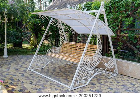Empty wooden swing with white decorative metal frame in the garden free space. Wooden furniture for garden. Swinging bench in the garden
