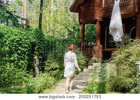 Beautiful redhead bride in silk dressing gown running barefoot to her wedding dress hanging on wooden house in the forest free space. Wedding morning preparation in sunny summer day