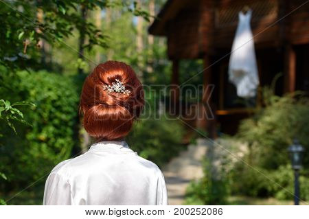 Back View Of  Beautiful Redhead Bride In Gown With Elegant Hairstyle With Wedding Dress On Wood Hous