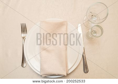 Table With White Plate, Crystal Wineglasses, Linen Beige Napkin And Cutlery On Tablecloths, Top View