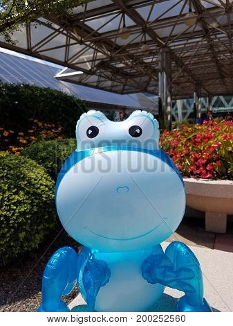 a large blue balloon animal with flowers in the background