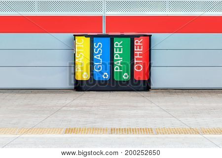 Multicolored bin for separate waste collection on the railway station platform.