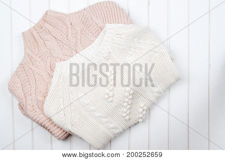 Two Modern Knitted Sweaters On White Wooden Background.